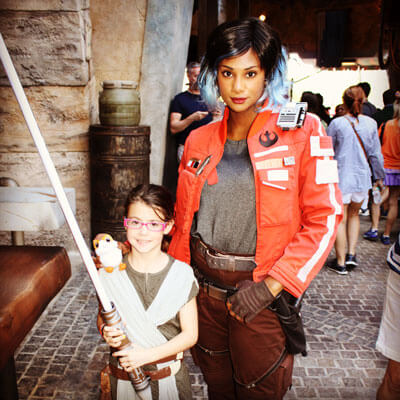 Vi Moradi poses with a young rebel holding a lightsaber
