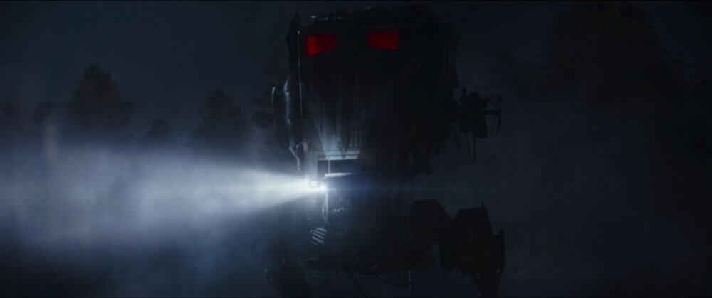 A two-legged walking tank with glowing red windows surveys the battlefield
